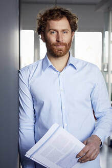 Portrait of a businessman with papers in office - RBF07266