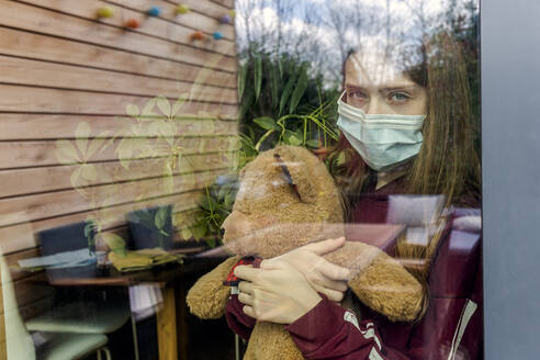 Portrait of girl with surgical mask and teddy bear behind window pane - SARF04513