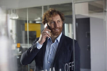Portrait of smiling businessman in office on the phone - RBF07319