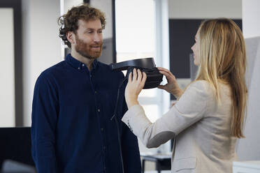 Businesswoman and businessman with VR glasses talking in office - RBF07325