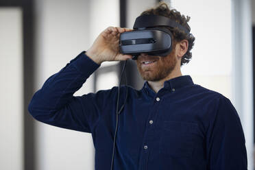 Businessman wearing VR glasses in office - RBF07328