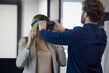 Businessman applying VR glasses on businesswoman in office - RBF07331