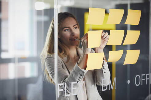 Businesswoman writing on adhesive notes on glass pane in office - RBF07343