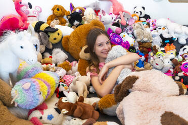 Girl sitting on couch, covered in cuddly toys - SARF04517