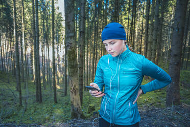 Young female jogger using smartphone in the woods - VTF00619