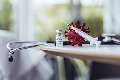 Model of coronavirus with vaccine on table with stethoscope - MFF05377