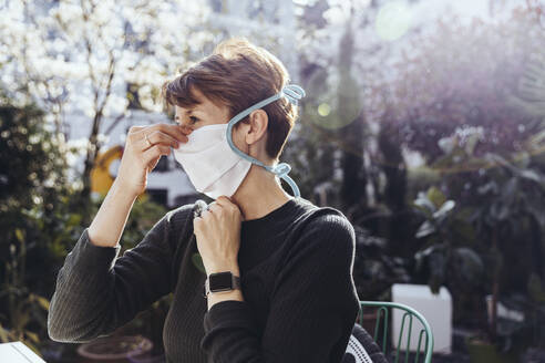 Woman siting in garden, putting on face mask - MFF05386