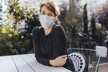 woman with face mask sitting n the garden - MFF05389