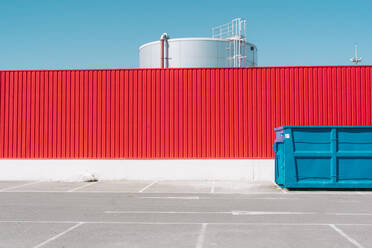 Blue container in front of red wall in industrial setting - ERRF03115