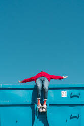 Young man relaxing on blue container, leaning backwards over edge - ERRF03121