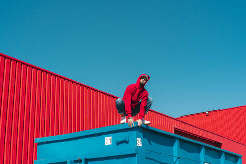 Young man wearing red hooded jacket crouching on edge of container in front of red wall - ERRF03124
