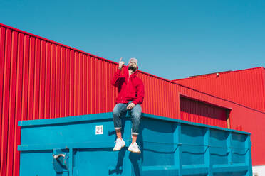 Young man wearing red hoodie, sitting on edge of blue container in front of red wall, raising forefinger - ERRF03127