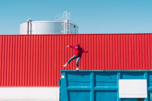 Young man wearing red hooded jacket balancing on edge of container in front of red wall in industrial setting - ERRF03130