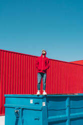 Young man wearing red hooded jacket standing on edge of container in front of red wall - ERRF03133