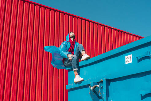 Young man wearing rain coat sitting on edge of blue container in front of red wall - ERRF03142