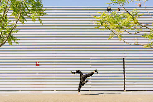 Man wearing black overall doing handstand in front of industrial building - ERRF03151
