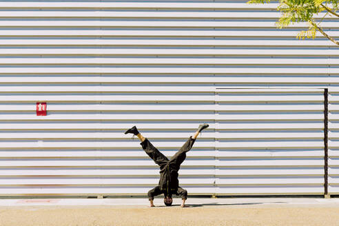Man wearing black overall doing handstand in front of industrial building - ERRF03154