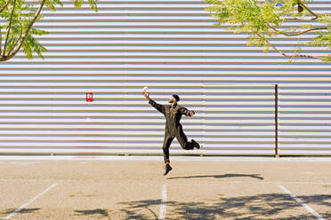 Man wearing black overall jumping in the air in front of industrial building - ERRF03163
