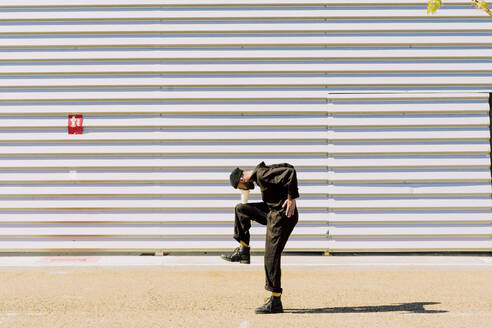 Man wearing black overall balancing with in front of industrial building - ERRF03166
