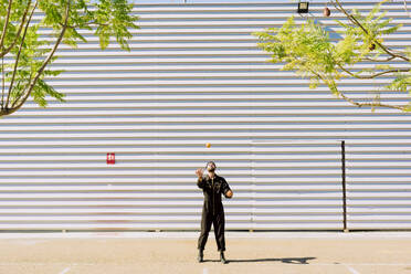 Man wearing black overall juggling with oranges in front of industrial building - ERRF03169