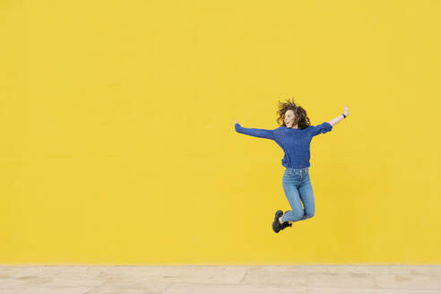 Young woman jumping in the air in front of yellow background - JCZF00031