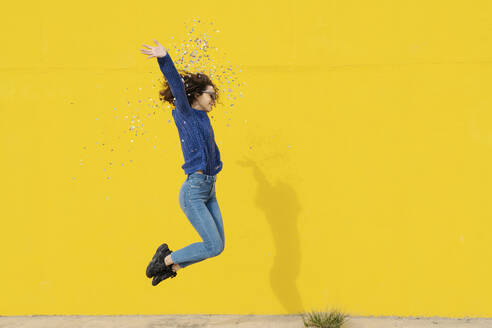 Young woman jumping in the air in front of yellow background throwing confetti - JCZF00034