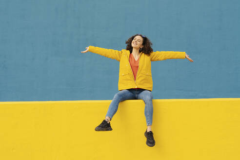Happy young woman sitting on yellow wall with arms outstretched - JCZF00043