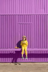 Little girl dressed in yellow sitting on bar in front of purple garage door drinking - ERRF03171