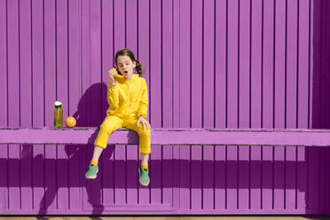 Little girl dressed in yellow sitting on bar in front of purple background playing with banana - ERRF03174