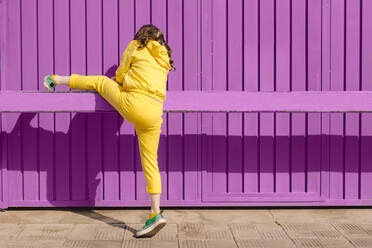 Back view of girl dressed in yellow climbing on bar in front of purple background - ERRF03177