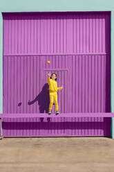 Happy little girl dressed in yellow balancing on bar in front of purple garage throwing orange in the air - ERRF03180