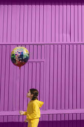Little girl dressed in yellow holding balloon in front of purple background - ERRF03186