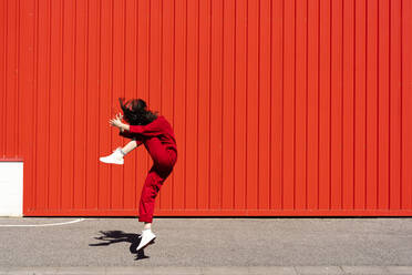 Woman dressed in red overall jumping in the air in front of red roller shutter - ERRF03189