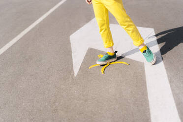 Girl stepping on banana peel on a street - ERRF03209