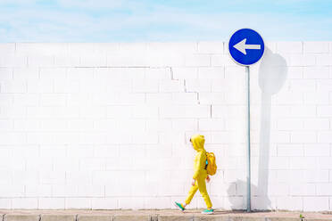 Girl walking at a traffic sign, direction left in front of a white wall - ERRF03212
