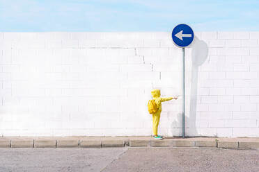 Girl with her toy on a traffic sign, direction left in front of a white wall - ERRF03215