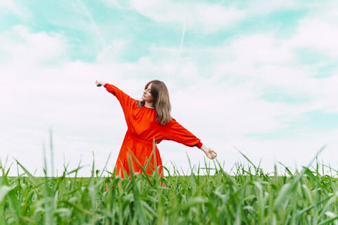 Woman wearing red dress dancing in a field with eyes closed - ERRF03233