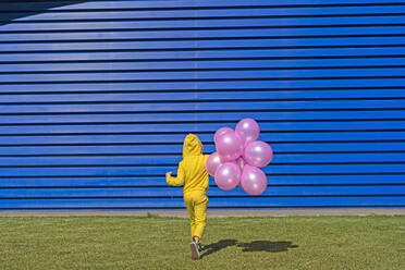 Back view of girl with pink balloons wearing yellow tracksuit walking in front of blue background - ERRF03242