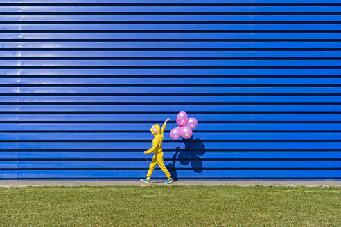 Little girl with headphones wearing yellow tracksuit walking in front of blue background with pink balloons - ERRF03245
