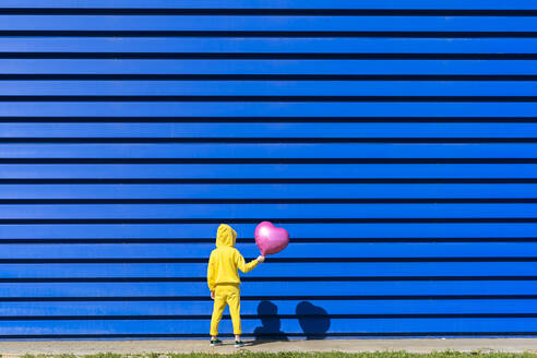 Back view of little girl with pink balloon wearing yellow tracksuit standing in front of blue background - ERRF03248