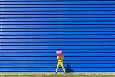 Little girl wearing yellow tracksuit standing in front of blue background hiding behind pink balloon - ERRF03251