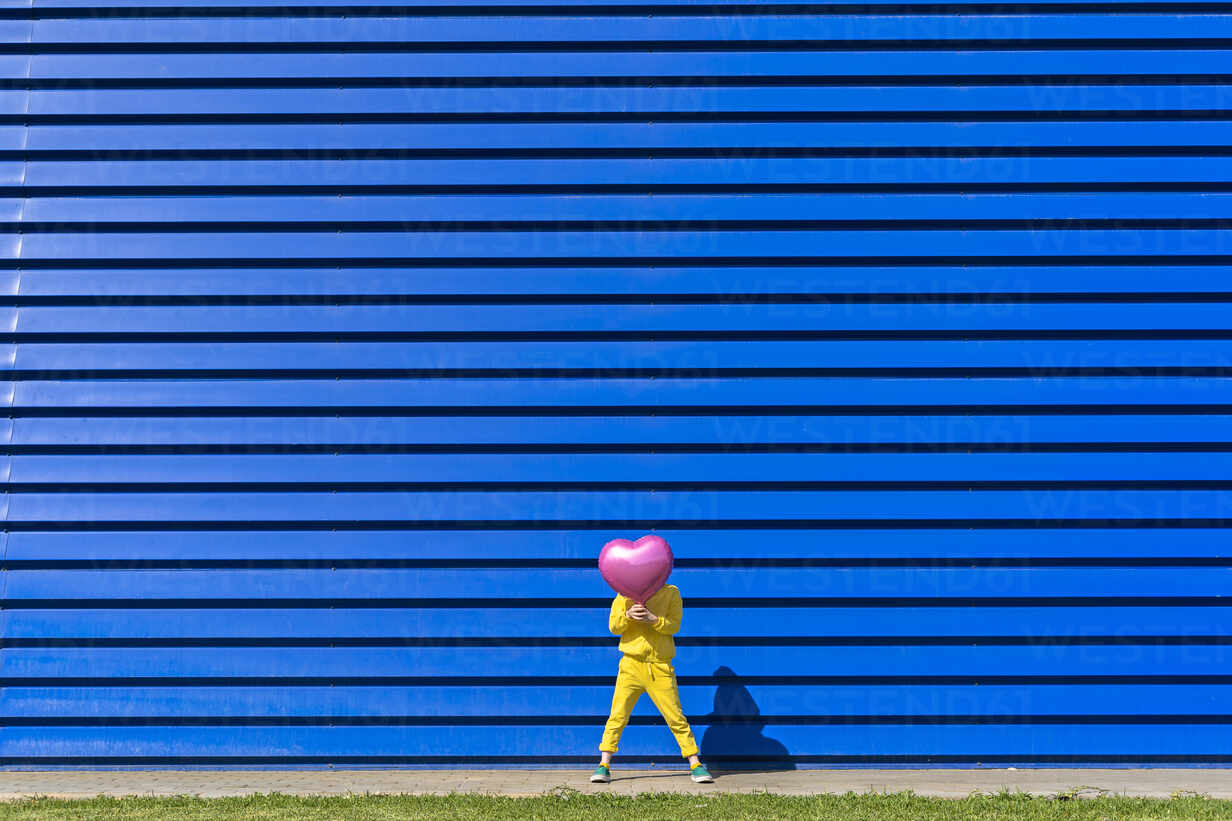 Little girl wearing yellow tracksuit standing in front of blue background hiding behind pink balloon - ERRF03251 - Eloisa Ramos/Westend61