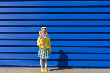 Little girl with pinwheel standing in front of blue background - ERRF03257