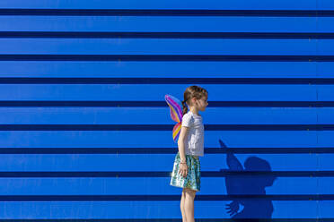 Little girl with colourful butterfly wings in front of blue background - ERRF03263