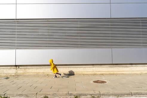 Little girl wearing yellow rain coat running on pavement - ERRF03266