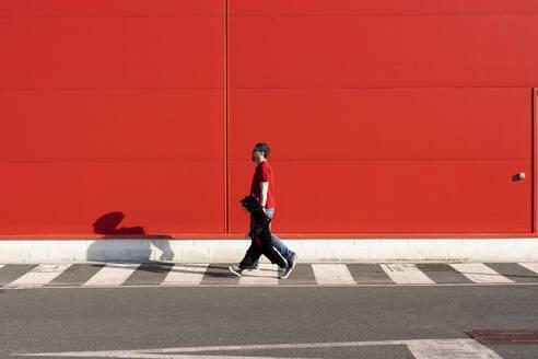 Man walking with his little girl wearing black fancy dress on zebra crossing - ERRF03269