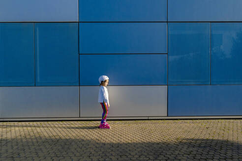 Little girl with safety helmet and inline skates standing at sunlight - ERRF03275