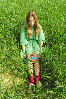 Young woman wearing green dress sitting on a field looking at mirror - ERRF03278
