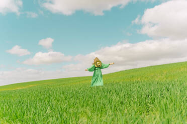 Back view of woman wearing green dress walking on a field - ERRF03284