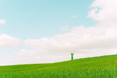 Young woman wearing green dress standing on a field with hands raised - ERRF03287